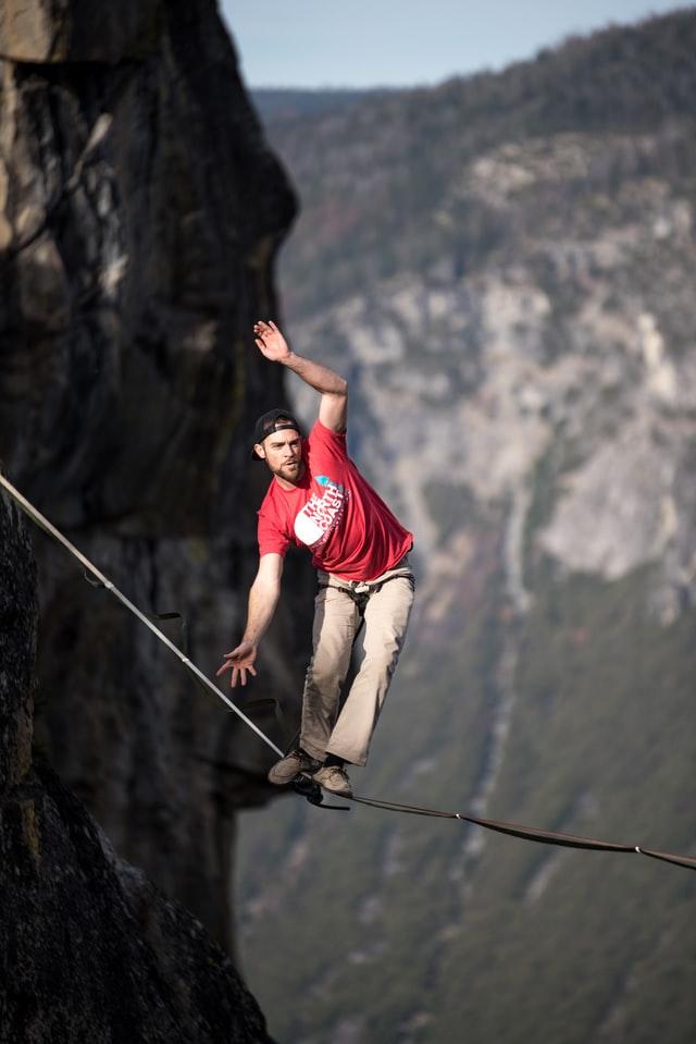 בחור הולך על חבל דק מעל רכס הרים - תמונה להמחשה