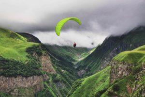 בחור עם מצנח באוויר בסביבת הרים